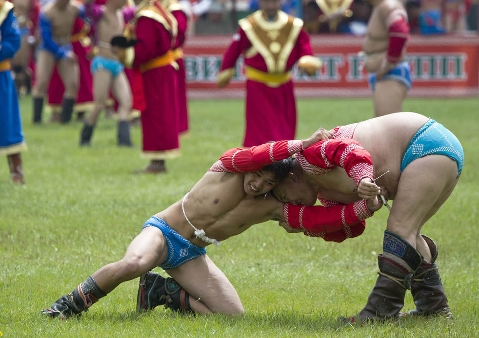 Mongolian wrestlers compete at a traditional wrestling competition during the Naadam Festival in Ulan Bator, Mongolia Wednesday, July 11, 2012. Mongolians celebrate the anniversary of Genghis Khan's march to world conquest on July 11 with the annual sports festival featuring traditional Mongolian events including wrestling, archery, and horse racing. (AP Photo/Andy Wong)